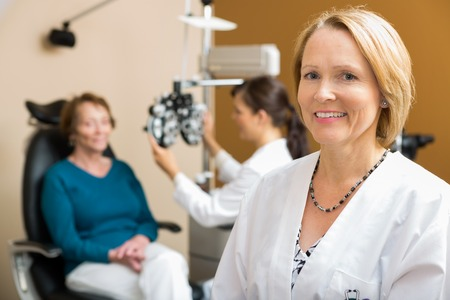 25762026 - portrait of confident optometrist with colleague examining patient in background