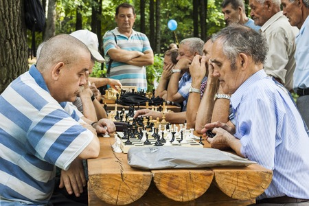 61437013 - people in the city park play chess. city cheboksary, chuvash republic, russia. 08/21/2016